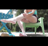 Gorgeous blonde with steaming hot body shows her hot boobs wearing her blue bra and jeans skirt before she pulls down her white panty hose and screws her crack with a gray and blue vibrator on a green monoblock chair by a pool.