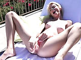 Sexy stunning blonde babe inserts a huge dildo in her pussy while outdoor