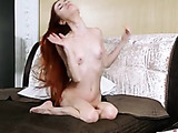 Red haired hottie is naked on the bed, rubbing her moist twat