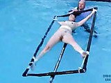 Blonde girl is tied to a rotating device that dips in pool!