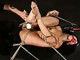 Muscular lady with red ball gag is bound on table and flogged.