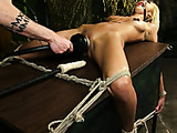 Table-bound blonde babe's pussy is vibrated while asshole is dildo-fucked.