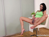 Slut in green top uses a dildo while she pees in the bedroom.