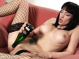 Seductive slut in fishnets rides a bottle on the chair.