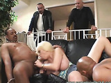 Foxy blonde teases two hunk studS with her steaming hot body in blue blouse and jeans skirt then gets naked and lets his husband watch as she lets them bang her while she suck their dicks on a black couch.