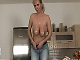 Blonde wearing yellow rubber gloves pours oil on her big tits in the kitchen