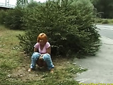 Red haired slut takes a pee behind a bush near a highway