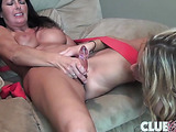 Brunette girl lies on white couch and helps brunette fuck her pussy.