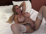 Blonde with massive tits in white stockings and heels lay down on bed so redhead can make her wet