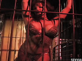 Hot redhead under dark light in a cage while showing her body to the cameras