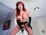 Sexy redhead with black stockings and leather gloves shoves a big stick up her pussy