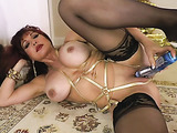 Redhead wearing gold outfit wrapped her tits shows off her rotating dildo before fucking it