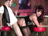 Busty redheaded MILF in black dress sucks a young cock at the bar