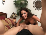 Brunette milf with tanned skin gives a rimjob in the bedroom