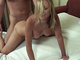 Sexy blonde milf in pink sucks a hard shaft on the sofa bed.
